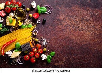 Food ingredients for italian pasta, spaghetti on brown dark background. Copy space of your text
