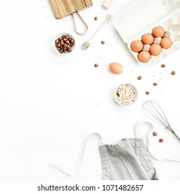Food ingredients on white background. Cooking flat lay, top view concept. Eggs, apron, cutting board, hazelnut, cereals on white background. Mock up.