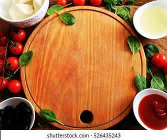 Food ingredients for pizza on wooden table. Top view.