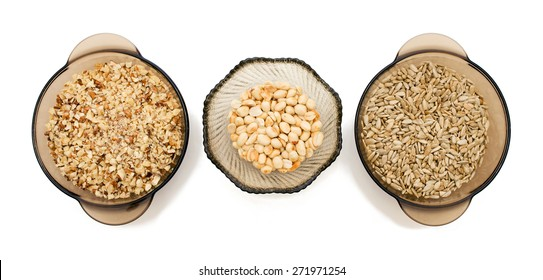 Food ingredients: walnuts crushed, peeled sunflower seeds, nuts, peanuts in a glass on a white background, top view