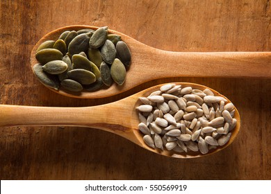 Food ingredients in wooden spoon on wooden background. Pumpkin seed and sunflower seed