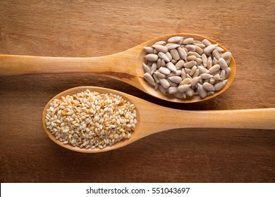 Food ingredients in wooden spoon on wooden background. Sunflower seed and sesame