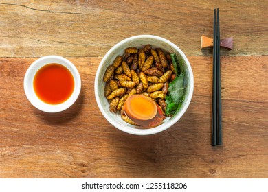 Food insect is the healthy meal high protein diet in the bowl on wooden background. Concepts for edible insects contributing to food security and food revolution. Top view, Selective focus.