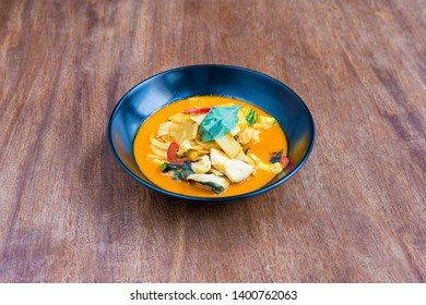 Thaï Food: Kaeng curry, chicken with red curry sauce and coconut milk, on a wooden table.
