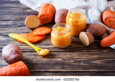 Food for kids, children's lure, organic puree from boiled potatoes and carrot in small glass jars on a dark rustic wooden background
