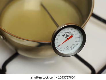 Food kitchen thermometer close up. Measuring heating liquid temperature. Cooking food & kitchen concept chef with thermometer measuring temperature in sugar syrup. Food safe thermometer in restaurant