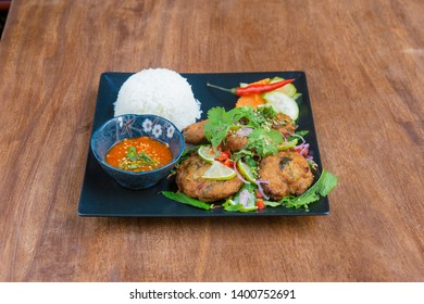 Thaï Food: Laab Chicken fried pickled with herbs, served on a wooden table.