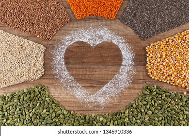 Food with love concept with various seeds and grains in radial stripes originationg in heart shape drawn in flour - copy space in center
