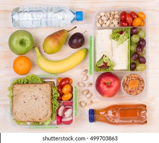 Food for lunch, lunchboxes with sandwiches, fruits, vegetables, and drinks, top view
