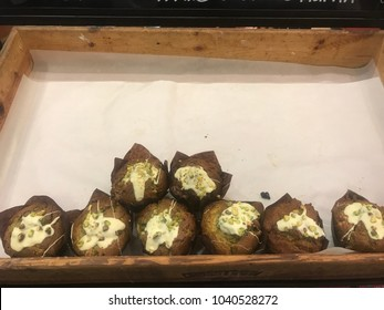 Food market stall, date and pistachio muffins, baked goods in wooden box