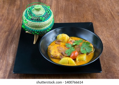 Thaï Food: Massaman Gai, curry massaman chicken with rice, served with a small traditional basket for rice - on a wooden table.