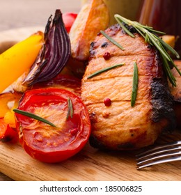 Food, meat, roast pork. Meat barbecue with vegetables on wooden surface. Meat steak. Beef steak bbq. Tomatoes, peppers, spices for cooking meat.