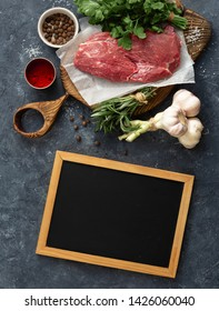 Food menu. Cooking table with blank chalk board and beef meat, vegetables, spices, herbs top view