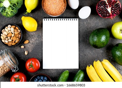 Food Mockup Recipe concept. Green vegetables, tomatoes, nuts, fruits, lentils, chickpeas, greens and empty notebook blank on grey concrete table. Flat lay, top view, copy space