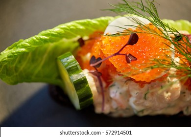 food, new nordic cuisine and cooking concept - close up of toast skagen with shrimps, lemon mayonnaise, caviar and buttery bread on plate