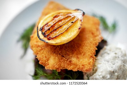 food, new nordic cuisine, dinner, culinary and cooking concept - close up of breaded fish fillet with tartar sauce and oven-baked beetroot tomato salad on plate
