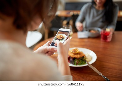 food, new nordic cuisine, technology and people concept - women with smartphones having breaded fish fillet with tartar sauce and oven-baked beetroot tomato salad for dinner at restaurant