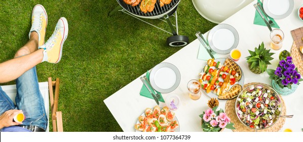 Food on the table and man holding a drink - grill party from the top