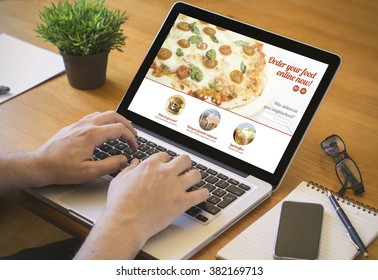 food order concept. Close-up top view of a coolhunter ordering pizza with a laptop. all screen graphics are made up.