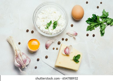 Food organic ingredients: cottage cheese, egg, garlic and parsley on white rustic concrete background. Top view, flat lay.
