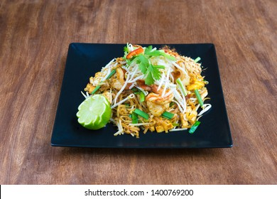Thaï Food: Pad Thai Goong shrimp, served on a wooden table.