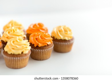 food, pastry and confectionery concept - cupcakes with buttercream frosting over white background