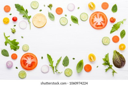 Food pattern with raw ingredients of salad. Various vegetables lettuce leaves, cucumbers, tomatoes, carrots, broccoli, onion and lemon flat lay on white background.