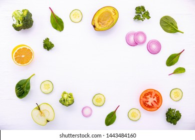 Food pattern with raw ingredients of salad, lettuce leaves, cucumbers, tomatoes, carrots, broccoli, basil ,onion and lemon flat lay on white wooden background.
