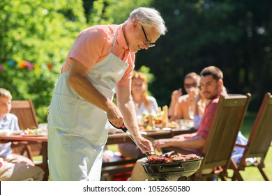 food, people and family time concept - senior man cooking meat on barbecue grill at summer garden bbq party