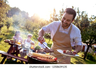 Food, people and family time concept.Young man cooking meat on barbecue grill at summer party.