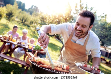 Food, people and family time concept.Young man cooking meat on barbecue grill at summer garden  party.