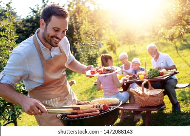 Food, people and family time concept.Young man grilling sausages on barbecue at summer garden party .