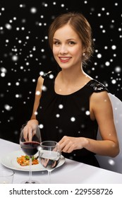 food, people, technology and holidays concept - smiling woman with tablet pc eating main course at restaurant over black snowy background