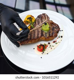 Food perfectionist. Styling meal with precision concentration and excellence. Restaurant serving