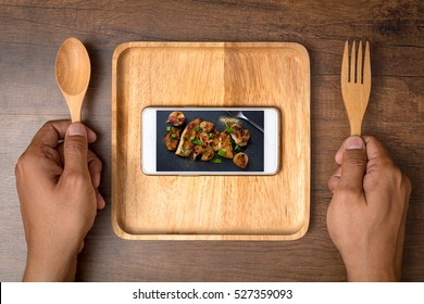 Food photo in smartphone with two hand holding a spoon and fork. The food and social media concept