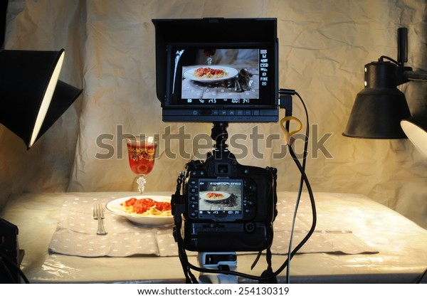Food photographer with camera and monitor.