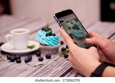 Food photography for the blog. Female hands shoots a photo of cupcakes on a smartphone.Food blogger shoots coffee and cupcakes. Food blog. Selective focus.