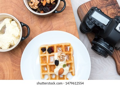 Food photography. Flat lay image of dessert meal with camera. Sweet fruit and nut waffles with fresh cream with waiting studio camera.