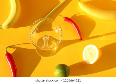 Food photography of a glas and several ingredients, including a lemon, lime, bananas, lemongras and chilies casting long shadows on a colorful yellow background.