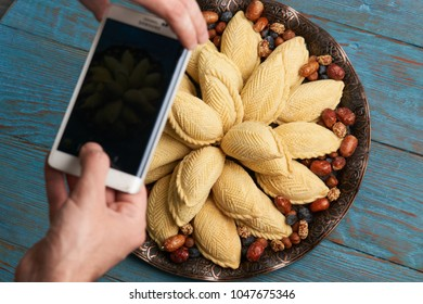 Food photography of Novruz tray with Azerbaijan national pastry shekerbura on wooden table background. Taking food photo with mobile phone for social networks