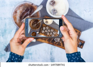 Food photography with phone. Woman hands make smartphone photo of in cafe. Sweet vegan protein energy balls dessert. Top above view