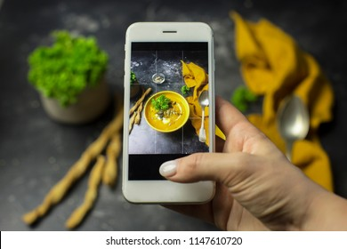 Food photograpy of pumpkin cream soup with croutons and parsley at dark background. Homemade food photo for social networks. Top view mobile phone photo of pumpkin cream soup/