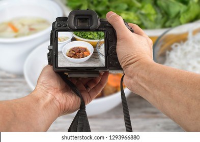 Food phototography concept. Man's hands holding a camera taking picture of an Asian meal set