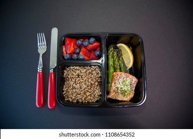 A food planning plastic container with a meal of baked salmon, grilled asparagus, quinoa and fruit for dessert.