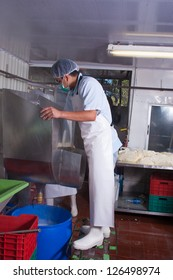 Food plant worker cleaning a stainless steel tank