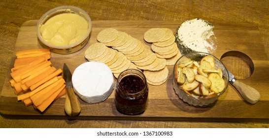 Food plate of carrot, flavoured sauce, crackers and hommus dip