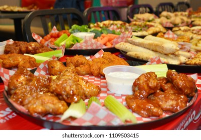 Food platter with chicken wings, bread, celery and pizza on the table.