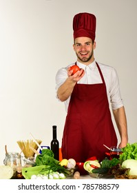 Food preparation concept. Chef with smiling face holds pair of red tomatoes on white background. Man in cook hat and apron holds ingredients. Cook offers tomatoes near table with vegetables and tools.