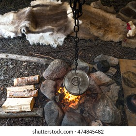 food is prepared on a fire in a sami lavvo