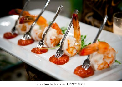 Food Presentation - Shrimp Cocktail served with miniature forks and cocktail sauce on a white plate